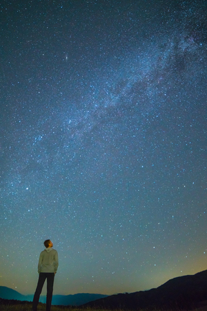 The man stand and look to the sky with stars. night time Imagens