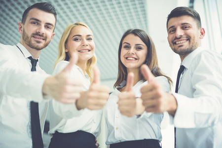 The four happy people thumb up Stock Photo