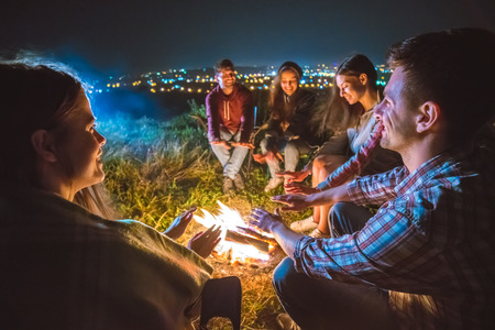 The five people warming hands near the bonfire. night time Stock Photo