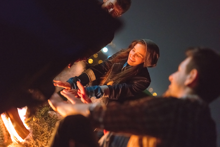 The happy people warming hands near the bonfire. night time
