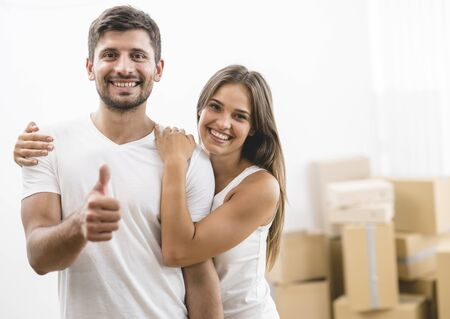 The woman and man thumb up on the background of the carton boxes Stock Photo