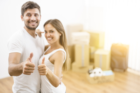 The happy woman and man gesture on the background of the carton boxes