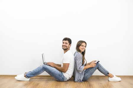 The smile couple sit with a laptop and a tablet near the empty wall
