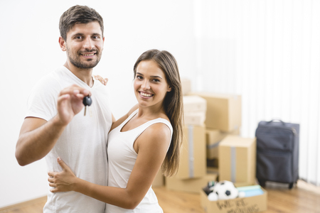The young couple hold keys from the new house