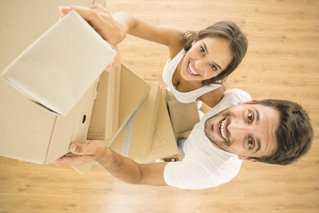 The man and woman hold a boxes and look to the camera. view from above