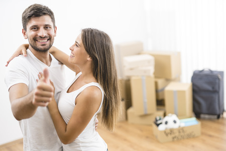 The man hugs a woman and thumb up on the background of boxes