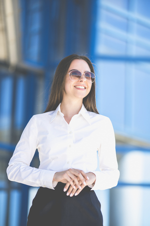 The happy businesswoman in sunglasses stand on the background of the building