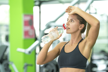 The sportwoman drink a water in the fitness club