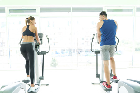 The sportsman and sportswoman in the cardio apparatus