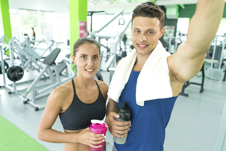 The happy sportsman and sportswoman make a selfie in the sport center