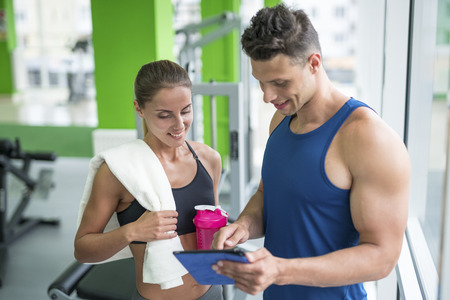 The woman discuss with a fitness instructor with a tablet