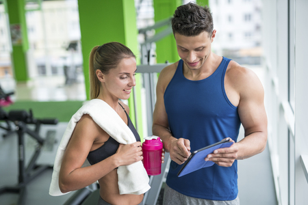show window: The woman discuss with a fitness instructor with a tablet