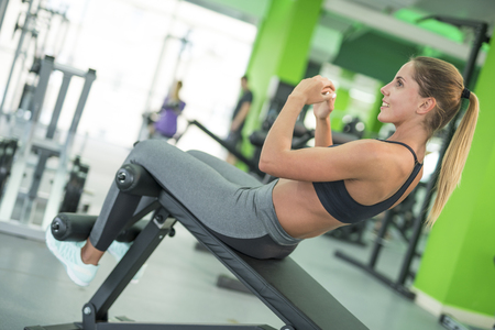 The woman doing abdominal exercise in the fitness club Stock Photo