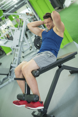 The sportsman doing abdominal exercise in the fitness club