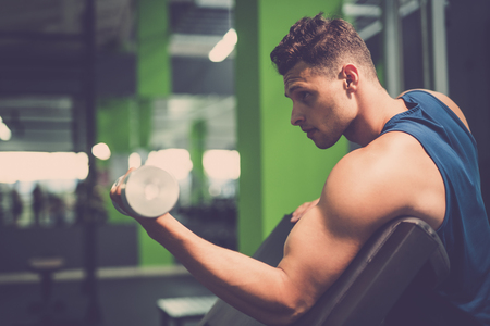 The sportsman doing biceps exercise with a dumbbell in the gym Stock Photo