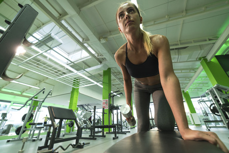 levantar peso: The sportswoman doing exercise with a dumbbell in the fitness center Foto de archivo