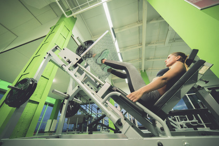 The woman doing exercise for legs in the sport center