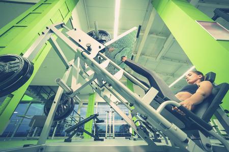 The sportswoman doing exercise for legs in the sport center Stock Photo