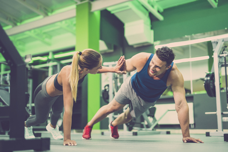The man and woman doing push up exercise and gesture in the gym