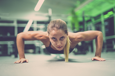 The sportswoman doing push up exercise in the gym Stock Photo
