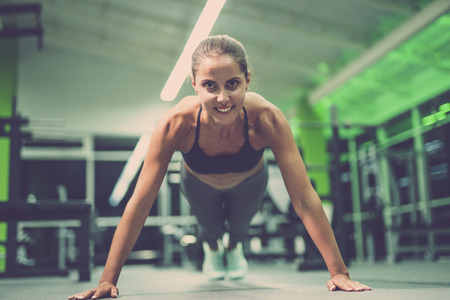 The happy sportswoman doing push up exercise in the gym Stock Photo