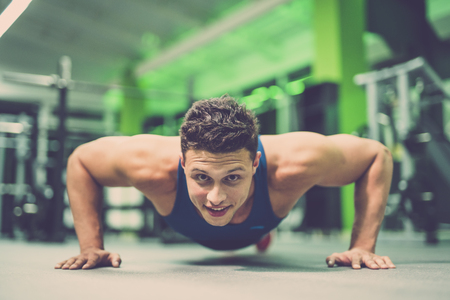 The happy sportsman doing push up exercise in the gym