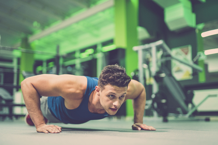 The sportsman doing push up exercise in the gym