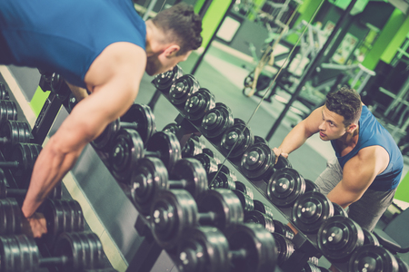The man take a dumbbell in the gym