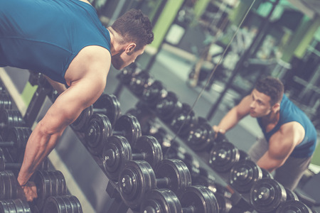 The sportsman take a dumbbell in the gym