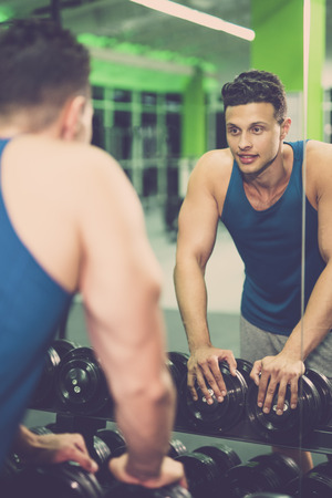 The happy sportsman look in mirror in the fitness club