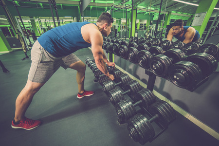The sportsman take a dumbbell in the fitness club