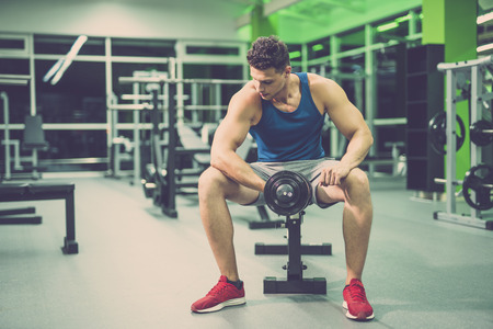 The sportsman doing exercise with a dumbbell in the fitness club
