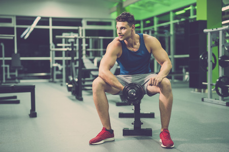 The happy man doing exercise with a dumbbell in the fitness club Stock Photo