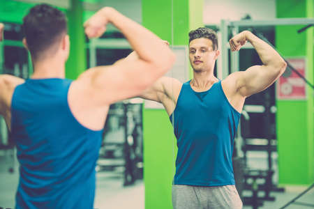 The sportsman pose in front of the mirror in the gym