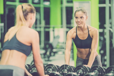 The sportswoman look in the mirror in the gym Stock Photo