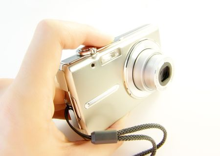 A hand holding a small digital camera