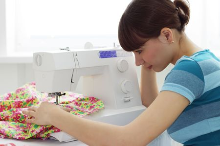 The girl works at sewing machine photo