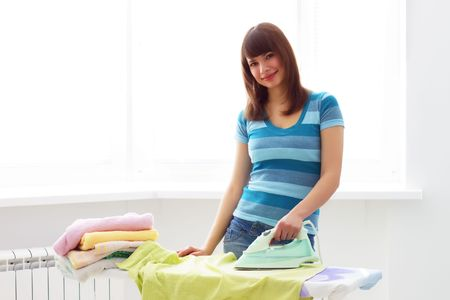 Young woman ironing on a light background photo