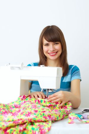 Girl and a sewing machine on a light background photo