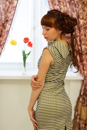 Beautiful girl standing near a window photo