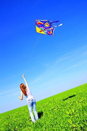 Girl playing with a kite on skyline Stock Photo - 7244735