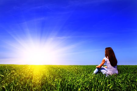 sit: Girl resting on the grass and looking at the sun