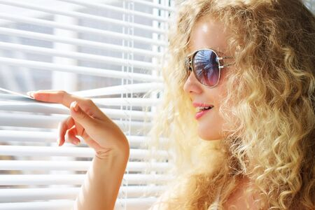 window blinds: Attractive girl looks out the window