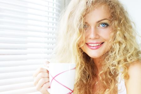 Beautiful girl near the window with a cup Stock Photo - 7396606