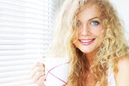 stores: Belle fille pr�s de la fen�tre avec une tasse