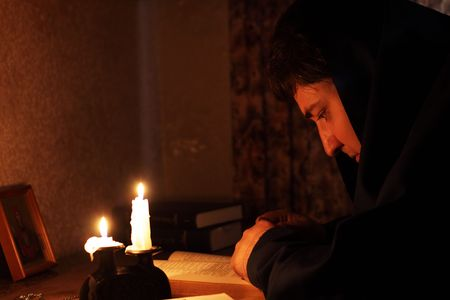 vestment: Man sitting by candlelight Stock Photo