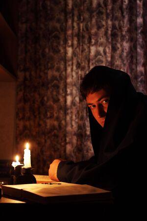 sotana: Hombre sentado por la luz de las velas