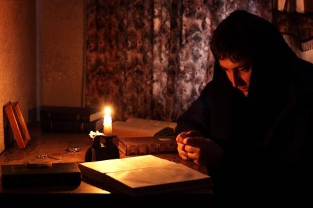mosquetero: Hombre sentado por la luz de las velas