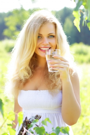 girl drinking water: Beautiful girl holding glass of water