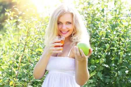 Beautiful girl is holding an apple and juice Stock Photo - 7436419
